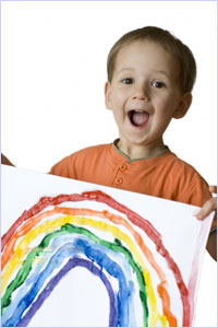 Picture of boy holding painting of a rainbow